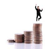 Ökande mynt och hoppa för affärsman som är lyckligt på maximumet Royaltyfria Bilder