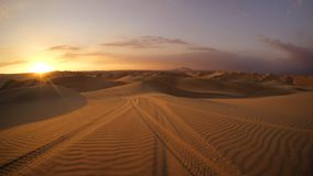 Öken på solnedgångtimmen med spår för gummihjul för dynbarnvagn i sanden i förgrunden royaltyfria bilder