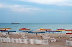 ?kenseascape med vita solstolar under f?rgrika strandparaplyer royaltyfri bild