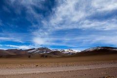 Öknen och berget över blå himmel och vit fördunklar på Altiplano, Bolivia Arkivbilder