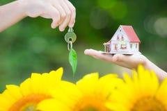 Ökologiehaus und -schlüssel in den Händen Stockfoto