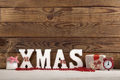 Ökologische, hölzerne Weihnachtsdekorationen Abstraktes Hintergrundmuster der weißen Sterne auf dunkelroter Auslegung Uhr, Kerze  Lizenzfreies Stockfoto