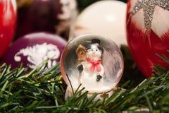 Ökologische, hölzerne Weihnachtsdekorationen Glänzende magische Glaskugel mit Schneemann und Weihnachtsbälle auf Baumzweig Schnei Lizenzfreies Stockbild