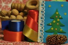 Ökologische, hölzerne Weihnachtsdekorationen Viele Feiertagsverzierungen und -geschenke Weihnachtsverzierungen mit Satingurt Stockbilder