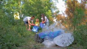 Ökologische Katastrophe, junge Freiwilligfamilie mit kleinem Kind sammelt Abfall in Abfalltasche in unfocused wann stock video footage