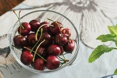 Ökologische Kirschen in der Glasschüssel, auf dem Tisch Stockfotos
