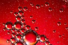 Öl auf Wasser-roter und silberner Blasen-Zusammenfassung Lizenzfreie Stockfotos