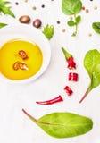 Öl des scharfen Paprikas, Oliven und Salatblätter Stockfotos