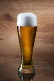 Öl Gass av öl på träbakgrund arkivbilder