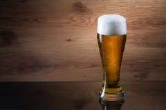 Öl Gass av öl på träbakgrund med copyspace arkivbild