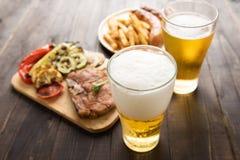 Öl i exponeringsglas med gourmet- biff och fransman steker på träbaksida royaltyfri foto
