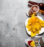 Öl med chiper och ketchup På gammal stenbakgrund arkivbild