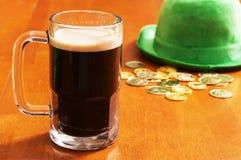 Öl med en irländsk hatt och guld royaltyfri fotografi