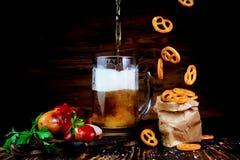 Öl med grillade korvar och den salta kringlan Arkivbild