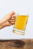 Öl med hållande glass öl för hand Arkivbilder