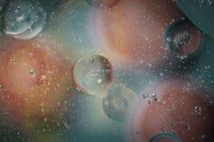 Öl mit Blasen auf einem bunten Hintergrund Stockfotografie
