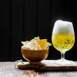 Öl och chiper på träbakgrund Royaltyfri Bild