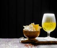Öl och chiper på träbakgrund Arkivbilder