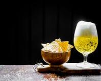 Öl och chiper på träbakgrund Arkivfoton
