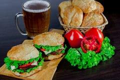 Öl och hemlagade hamburgarebullar med ingredienser för sallad för nötköttsmå pastejer nya Fotografering för Bildbyråer