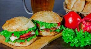 Öl och hemlagade hamburgarebullar med ingredienser för sallad för nötköttsmå pastejer nya Royaltyfri Fotografi