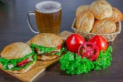 Öl och hemlagade hamburgarebullar med ingredienser för sallad för nötköttsmå pastejer nya Arkivbilder