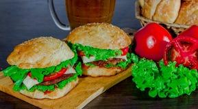 Öl och hemlagade hamburgarebullar med ingredienser för sallad för nötköttsmå pastejer nya Royaltyfria Foton