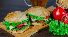Öl och hemlagade hamburgarebullar med ingredienser för sallad för nötköttsmå pastejer nya Arkivfoton