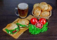 Öl och hemlagade hamburgarebullar med ingredienser för sallad för nötköttsmå pastejer nya Royaltyfria Bilder