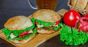 Öl och hemlagade hamburgarebullar med nötköttsmå pastejer och nya salladingredienser Arkivbild