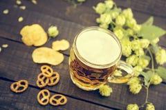 Öl och mellanmål på den svarta trätabellen Kallt öl för utkast i exponeringsglas Royaltyfria Bilder