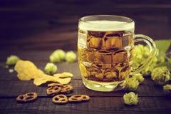 Öl och mellanmål på den svarta trätabellen Kallt öl för utkast i exponeringsglas Arkivfoto