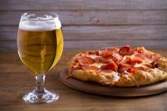 Öl- och peperonipizza på trätabellen Exponeringsglas av öl Öl- och matbegrepp royaltyfria foton