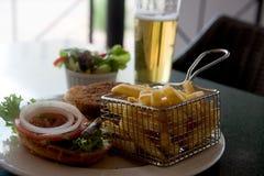 Öl och potatis med hamburgaren på tabellen royaltyfria bilder