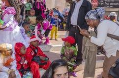 Öl-Sheva ISRAEL - mars 5, 2015: Den mörkhyade modern fotograferade på barn för en mobiltelefon tre i dräkter Arkivbilder