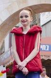 Öl-Sheva ISRAEL - mars 5, 2015: Flickagymnast med rött hår i ett rött omslag utan muffar - Purim Royaltyfri Fotografi