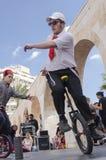 Öl-Sheva ISRAEL - mars 5, 2015: Tonåringpojke på cykelhjul, en står på den öppna etappen - Purim Arkivfoton