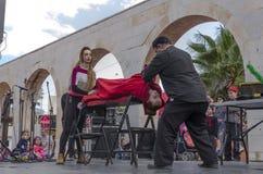 Öl-Sheva ISRAEL - mars 5, 2015: Trollkarlen utför på perioden för gataplatshypnos med flickan i rött - Purim Arkivbilder