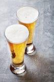 öl skummade upp fulla glass exponeringsglas ett två Arkivbild