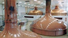 Öl som bryggas i metallbehållare i en lätthet på en fabrik stock video