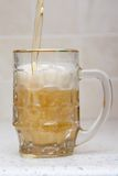 Öl som häller från flaskan in i exponeringsglas Royaltyfria Bilder