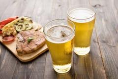 Öl som hälls in i exponeringsglas med biff på träbakgrund Arkivfoto