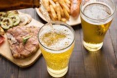 Öl som hälls in i exponeringsglas med gourmet- biff- och fransmansmåfiskar Royaltyfri Foto
