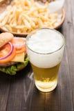 Öl som hälls in i exponeringsglas med gourmet- hamburgare och fransman Royaltyfri Foto