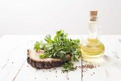 Öl und Koriander, Petersiliensamen auf einem weißen Holztisch Lizenzfreies Stockfoto