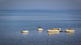 Öland costal view. Scattered rocks on the coast beach of Swedens island of Öland royalty free stock photos