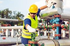 Ölarbeiter schließt das Ventil auf der Ölpipeline stockfoto