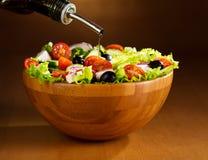 Ölen Sie das Gießen in Schüssel Gemüsesalat Lizenzfreie Stockbilder