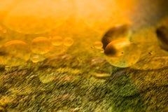Ölen Sie Tropfen und Blasen auf einer Metallgang-Maschinenoberfläche Weitwinkelobjektiv bedeckt durch Linsen-Kappe in der Mitte Lizenzfreie Stockfotografie