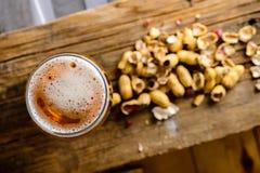 Ölexponeringsglas med mörkt kallt öl med bubblafradga och jordnötter på royaltyfria bilder
